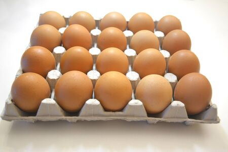 20 brown eggs in a carton box. Original look, eggs of a different shade. Light gray cardboard stand with eggs on a white background. and Idea for breakfast and cooking