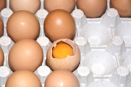 Broken egg among whole eggs in a package