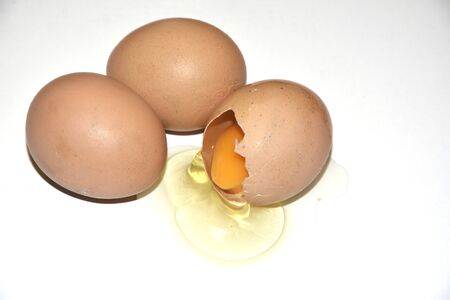 Three brown chicken eggs lie on an abelone background. One egg is broken, the yolk is visible. Idea for breakfast. Ingredients for cooking