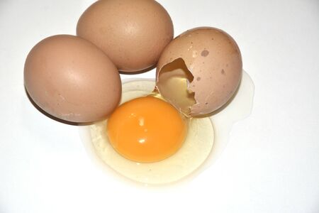 Three brown chicken eggs lie on an abelone Three brown chicken eggs lie on a white background. One egg is broken. Contained on the table, the yolk is visible. Idea for breakfast. Ingredients for cooking
