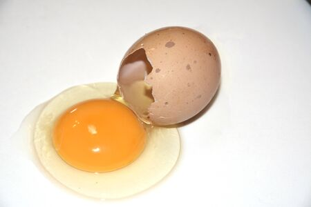 Brown broken egg on a white background. Content on the table, visible yolk. Idea for breakfast. Ingredients for cooking