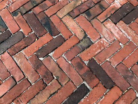 Brick texture. City sidewalk background. Abstract stone brick pattern. The texture of the sidewalk street. Stone laid herringbone