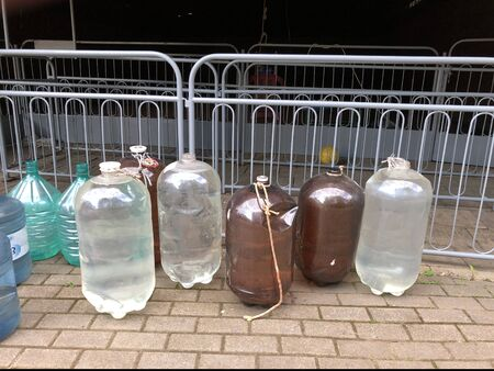 Large multi-colored bottles with dirty water. For technical work, water is poured into large bottles. On the street are large tanks with water