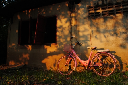 Old bicycle leaning against grungy barn photo