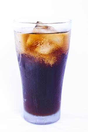 Glas gevuld met ijsblokjes en Cola soda op een witte achtergrond. Stockfoto