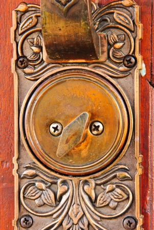 Color photo of a metal handle on a wooden door photo