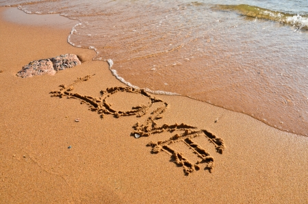Inscription love on the wet sand of the sea photo