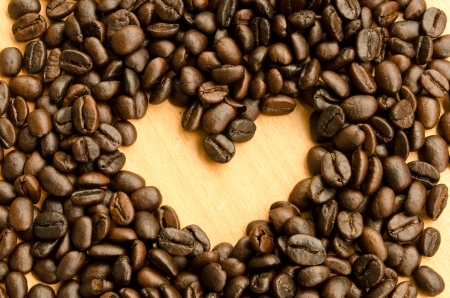 Heart shape made from coffee beans on wooden surface. photo