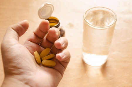 Hand holding yellow pills Standard-Bild