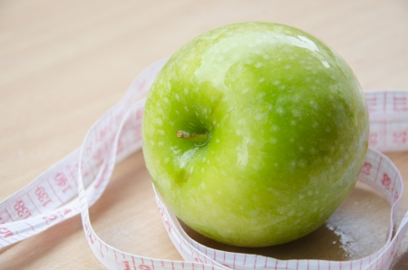 Green apple core and measuring tape  Diet concept photo