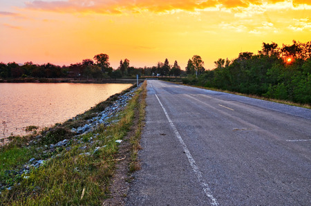 Rural road near river and nice sunset photo