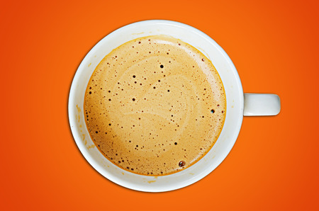 Cappuccino coffee cup and beans on a orange background photo