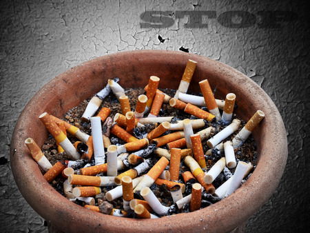 Cigarette addiction in ashtray on old wall