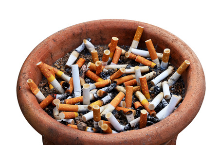 Cigarette addiction in ashtray on white photo