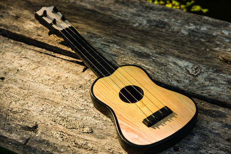 Toy acoustic guitar on vintage wood background, Close-up Stock Photo