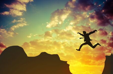 Businessman jumps over rocky mountain. Business and success concept Zdjęcie Seryjne