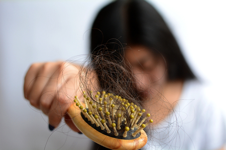 Hair loss, hair fall everyday serious problem, girl with a comb and problem hair on white background.