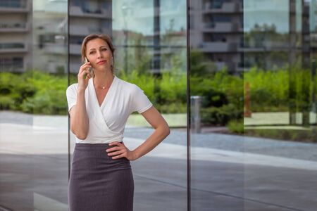 Businesswoman talking on the phone near the glass wall