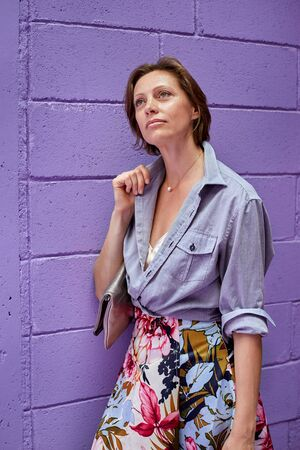 Young beautiful girl posing on a background of gently purple brick wall. She is wearing a fashionable bed ovetvet shirt and a long bright skirt.