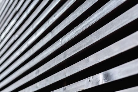 rhythmic strip of wooden slats, play of light. Cold tones, great contrast, perspective.