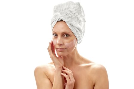 Beautiful woman with a towel on her head with patches for her eyes.