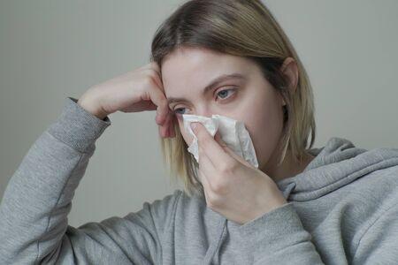 Portrait of Sick woman Sneezing into Tissue