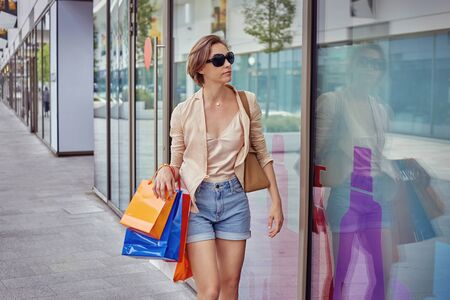 A young girl in a beige blouse and short denim shorts and glasses walks on a bright sunny day with shopping.