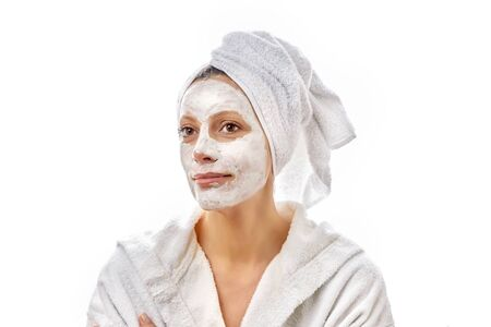 Beautiful young happy girl with a cloth mask.on her face smiles and enjoys the spa day.