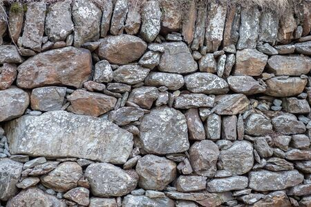 The stone wall is gray and brown. Stone barrier. 免版税图像