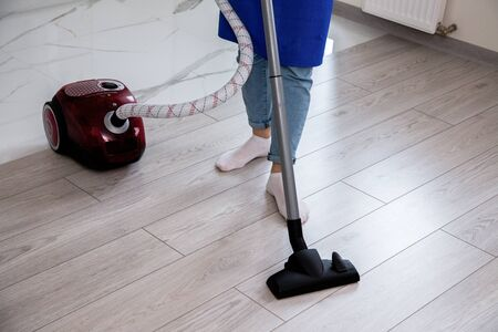 A girl in jeans and white socks is vacuuming the floor. Red vacuum cleaner