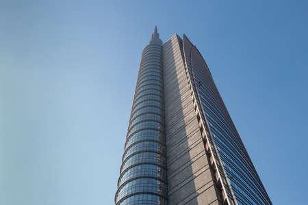 The top of a huge multi-story modern office building against a blue sky. 01.2020 Milan. Sajtókép
