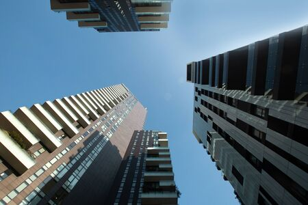 View of three multi-story futuristic buildings forming a circle with balconies against a blue sky. Banque d'images