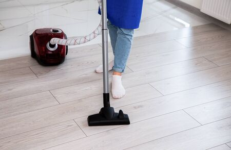 The girl in light jeans is vacuuming the floor Imagens