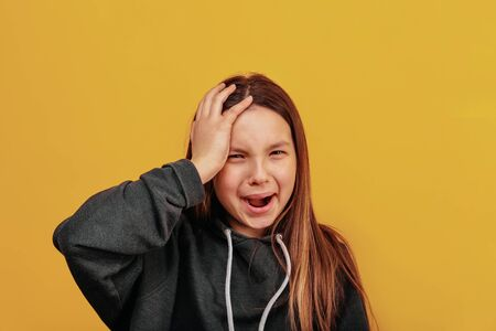 Beautiful young girl crying, screaming and holding his head.