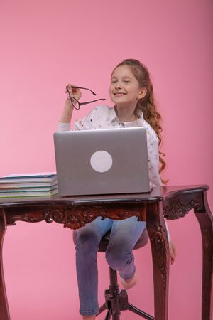 A girl in a white blouse and blue jeans holds in her hands glasses in a black frame sitting at a computer. Foto de archivo