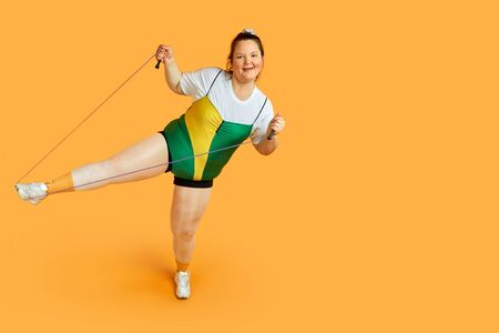 Doing sports with a skipping rope in hand. Sports Equipment. The desire to lose weight. Yellow background.