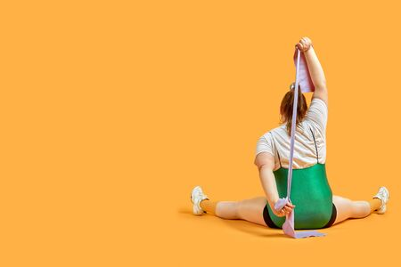 A fat girl sits with her back with a ribbon in her hands. Doing sports. Yellow background.
