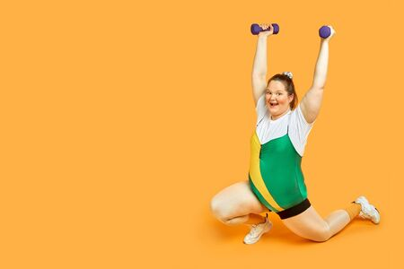 Fat girl goes in for sports with dumbbells in her hands, arms up in sportswear. Yellow background.