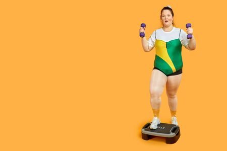 Sportswoman with dumbbells in hands training on the step platform. Yellow background. Stock fotó