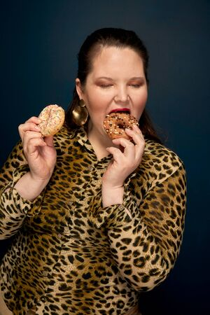 Fat girl eating donuts with an appetite. Leopard blouse. Overweight. Dark blue background.