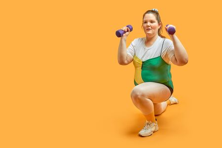 Sporting a fat girl with dumbbells in her hands, lunges exercise. Yellow background.