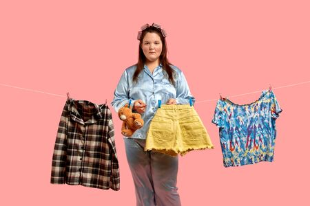 Sad fat girl in blue pajamas hangs clothes after washing. Pink background. 免版税图像