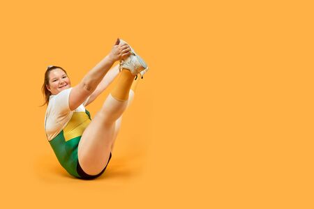 Bright full-time girl is engaged in sports in the hall. The legs are up. Yellow background. Stock fotó
