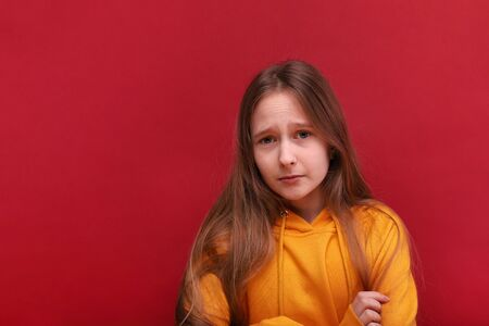A sad girl looks into the camera. Sad eyes. Red background. Banque d'images