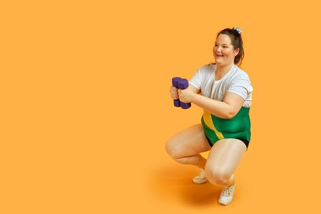 A fat girl goes in for sports, crouches, shakes her ass in sportswear with dumbbells in her hands. Yellow background.