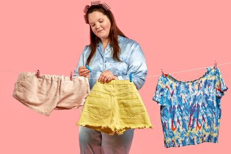 Fat beautiful girl hangs her washed clothes. Large size clothing. Pink background.