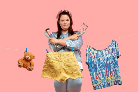 The fat girl was tired of household chores and angry. Clothes hang on the dryer. Pink background. Banque d'images