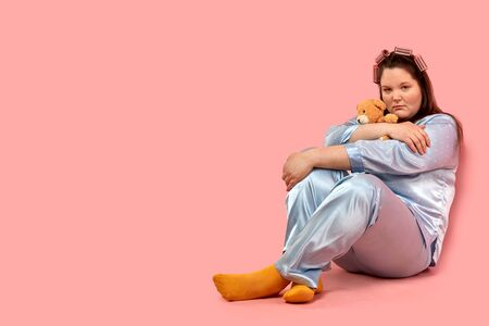 A fat sad girl sits on the floor with a bear cuddling. the concept of loneliness.