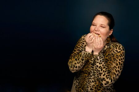 Overweight girl in a leopard blouse and with big earrings with a hamburger in her hand.
