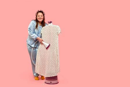 Happy fat girl uses a steamer for clothes. Pink background.